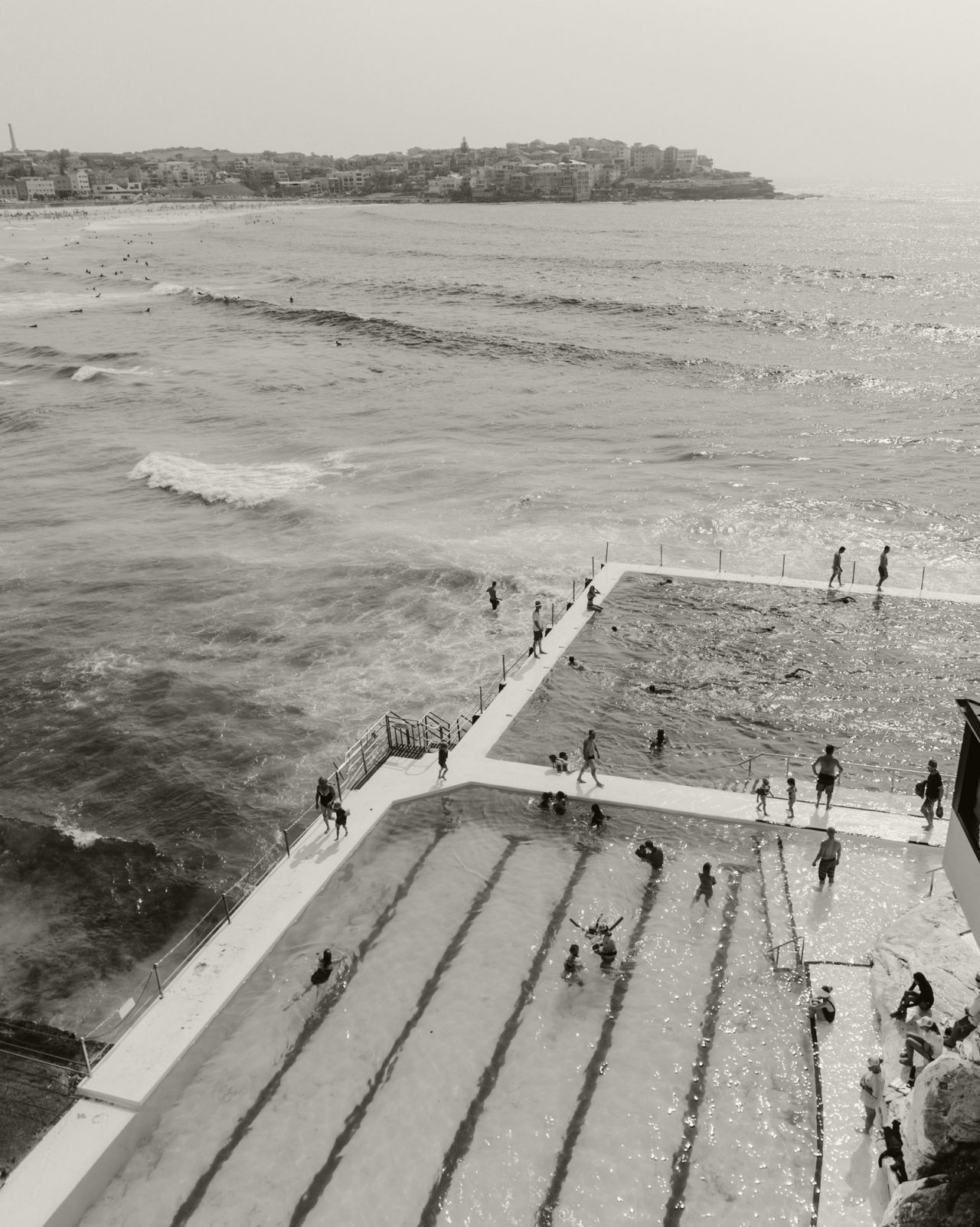 Black and white image of people swimming at a public beach in Sydney