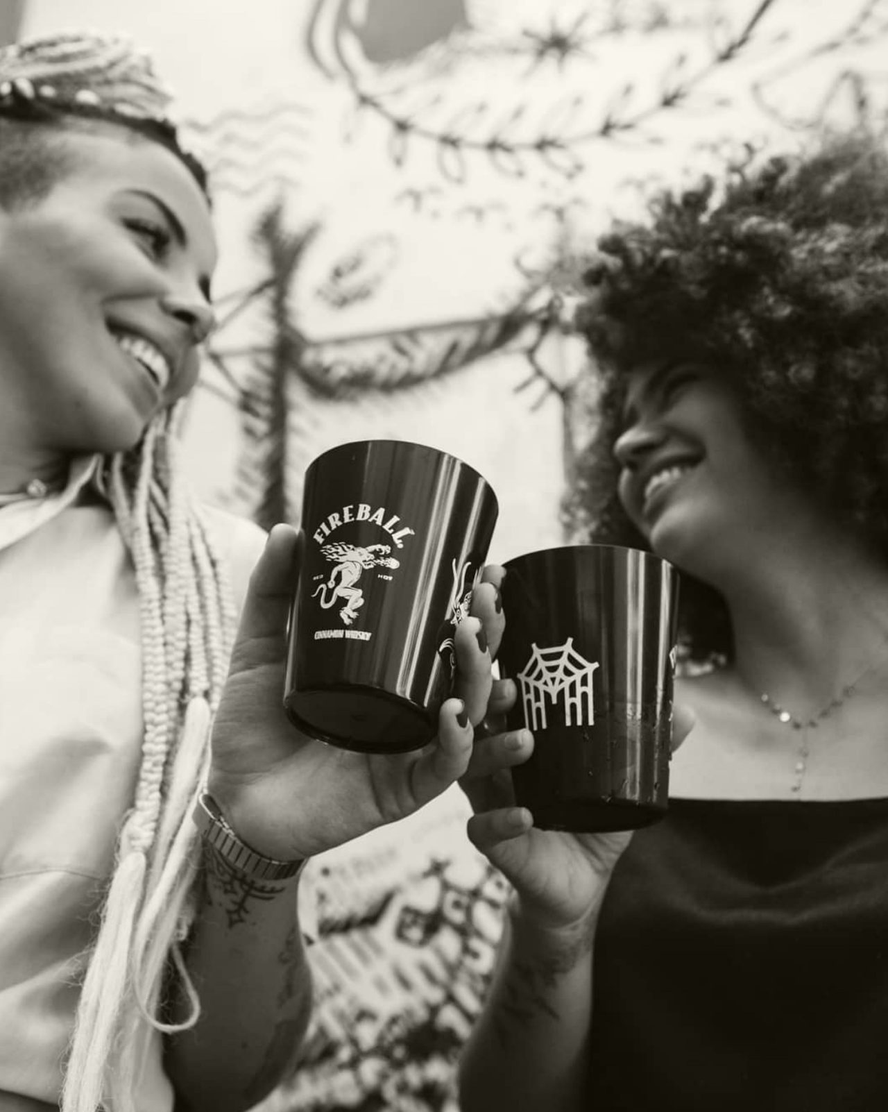 Black and white image of two women smiling and cheersing Fireball cups