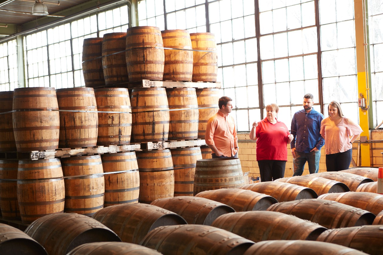 Two men and two women standing in the middle of barrels in a warehouse