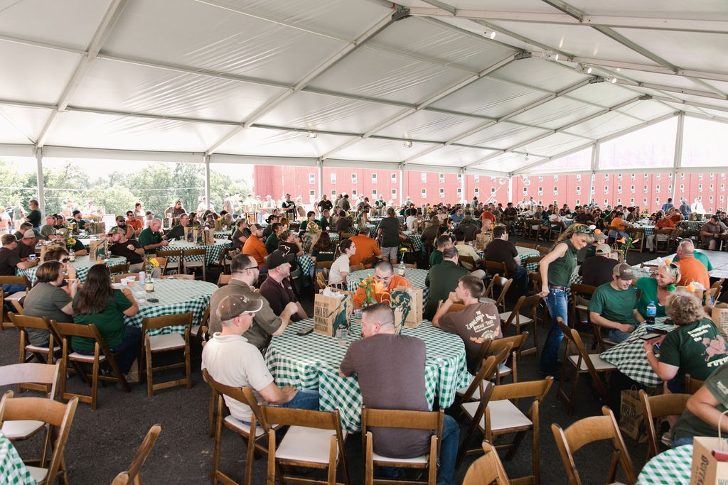 Large group of men and women at tables under a tent