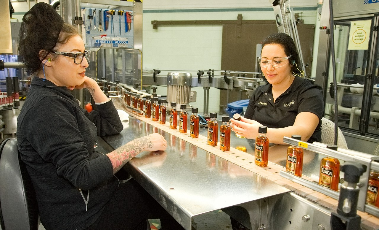 Two female employees inspecting bottles of Tuaca