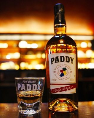 Paddy Irish Whiskey bottle and Paddy glass on bar top