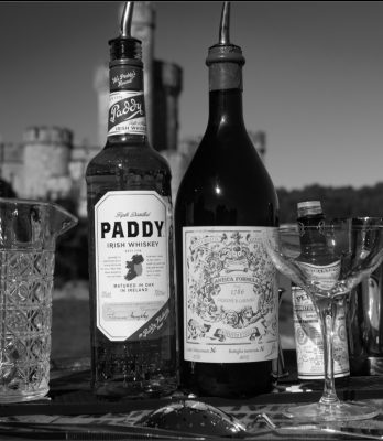 Black and white lineup of the ingredients for the Paddy Cocktail with castle in background