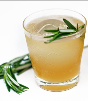 Closeup of a whiskey and ginger cocktail with garnish