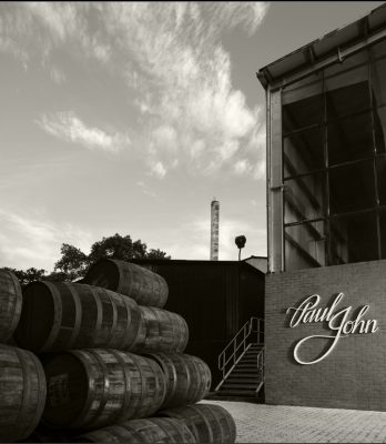 Black and white view outside Paul john Distillery with stack of barrels