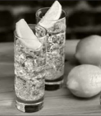 Black and white image of two tall cocktail glasses on table with lemon slices in each and whole lemons on table