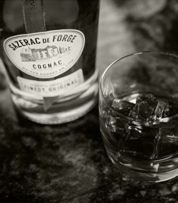 Black and white closeup of Sazerac de Forge Cognac bottle and old fashioned in rocks glass