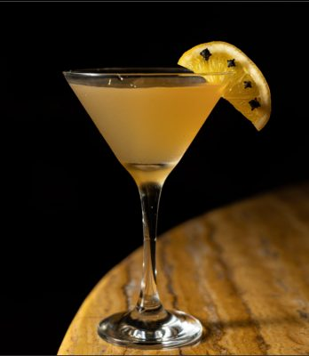 Closeup of yellow martini on wood table with black background