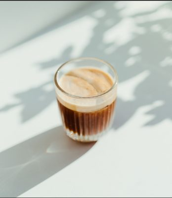 Coffee in glass on white table with tree shadows