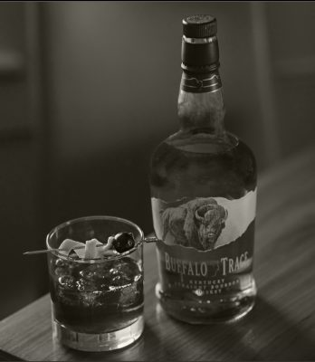 Black and white image of Buffalo Trace Bourbon cocktail and bottle on table