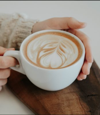 Female hands holding coffee mug with froth art