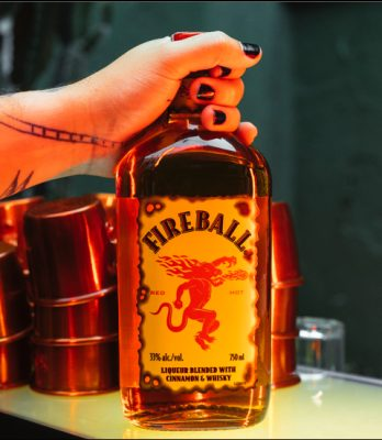 Download Tattooed hard holding Fireball bottle on bartop