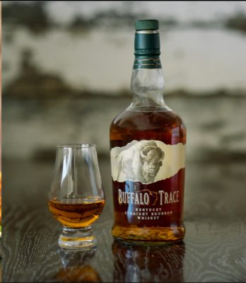 Download Neat pour of Buffalo Trace Bourbon and bottle on wood table