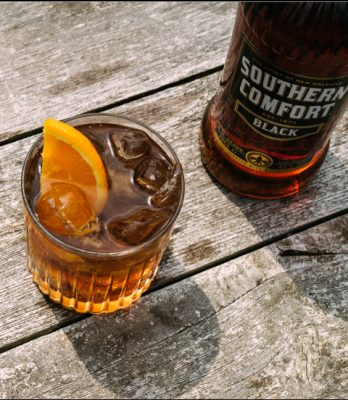 Download Closeup of a Southern Comfort Black cocktail and bottle on wood table