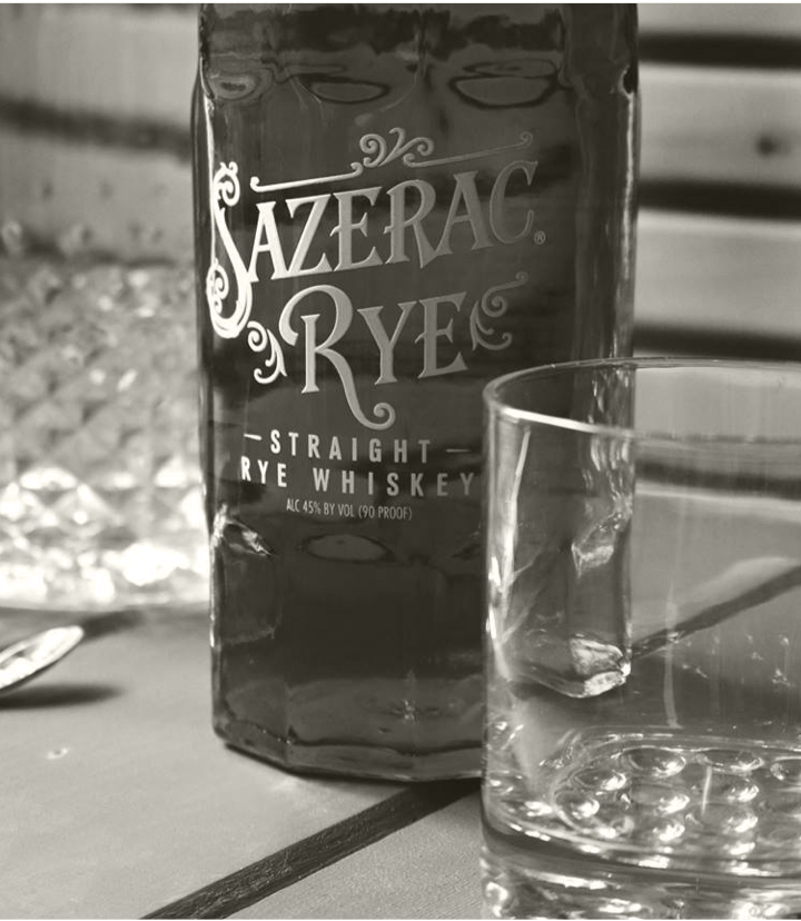 Black and white closeup of Sazerac Rye bottle and empty rocks glass