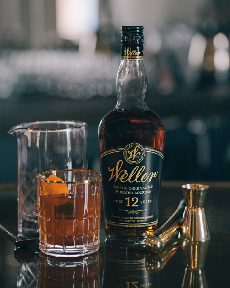 A custom drink made with Weller Aged 12 Years and garnished with a Orange slice