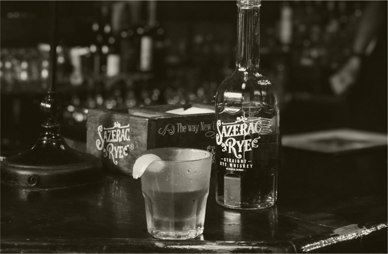 A black and white photo of a cocktail made with Sazerac Rye with lemon to garnish