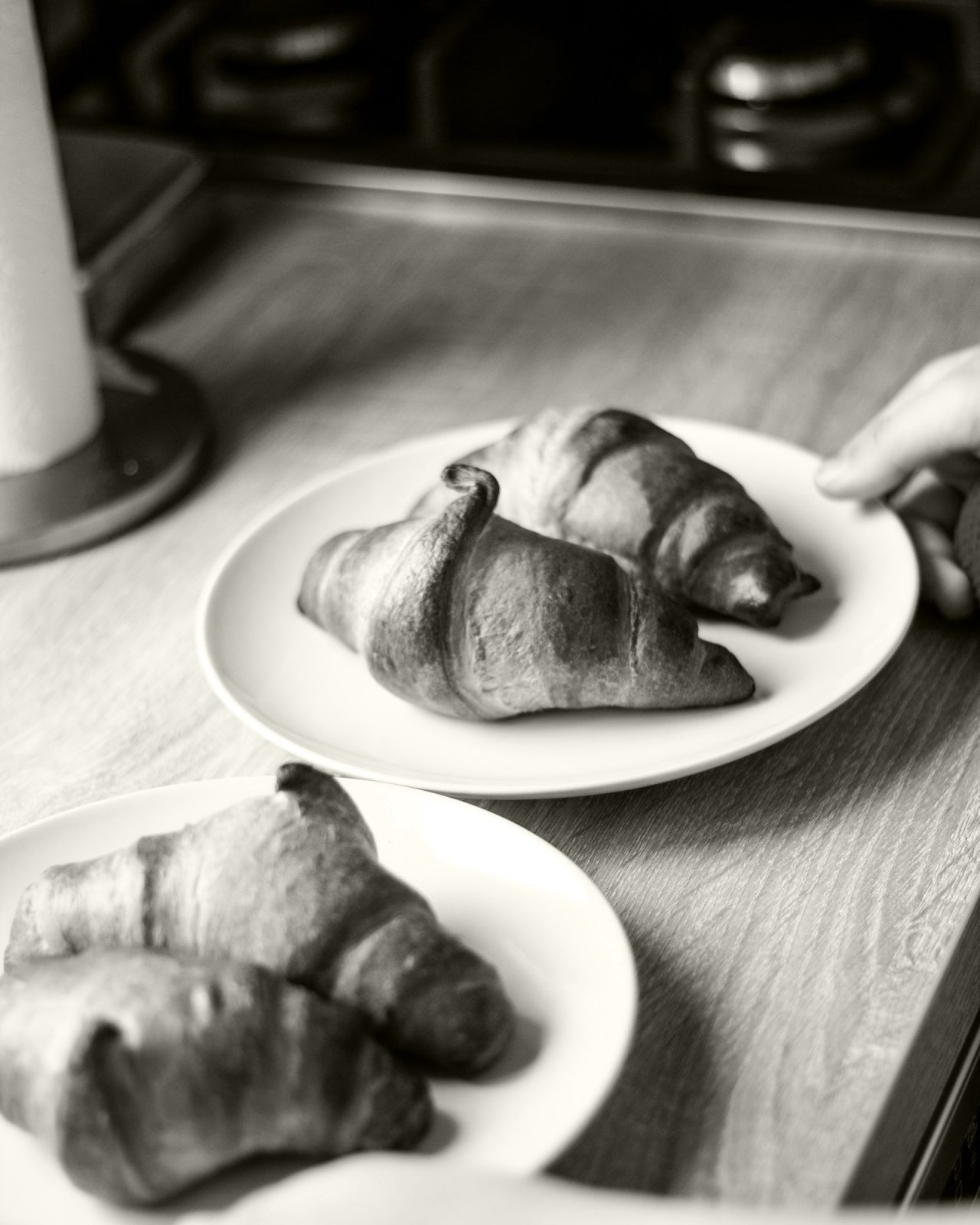 Black and white table with two plates of two croissants on each