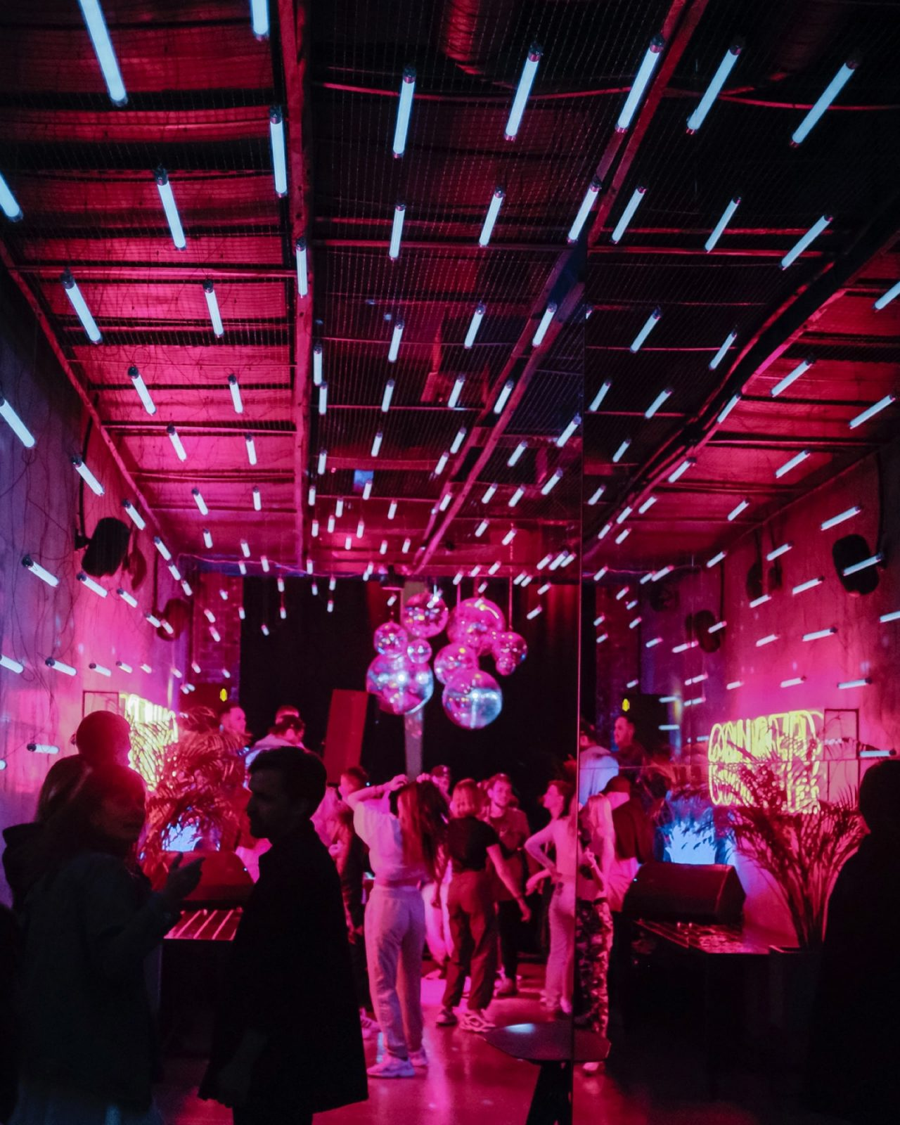 People dancing at a night club with disco balls and pink neon lights