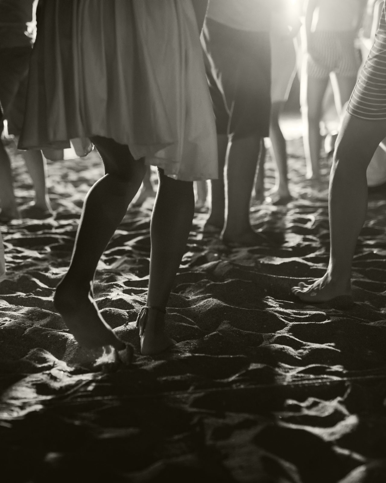 Black and white closeup of people's legs at a nighttime beach dance party