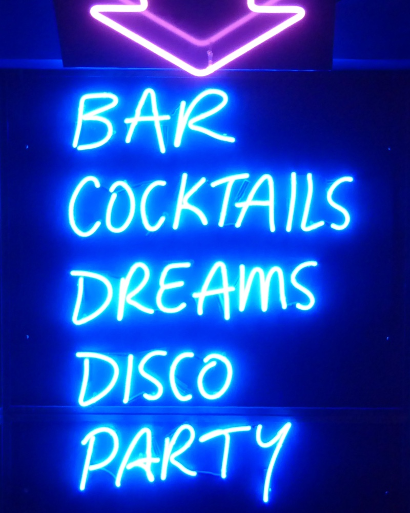 A sign that says bar, cocktails, dreams, disco, party