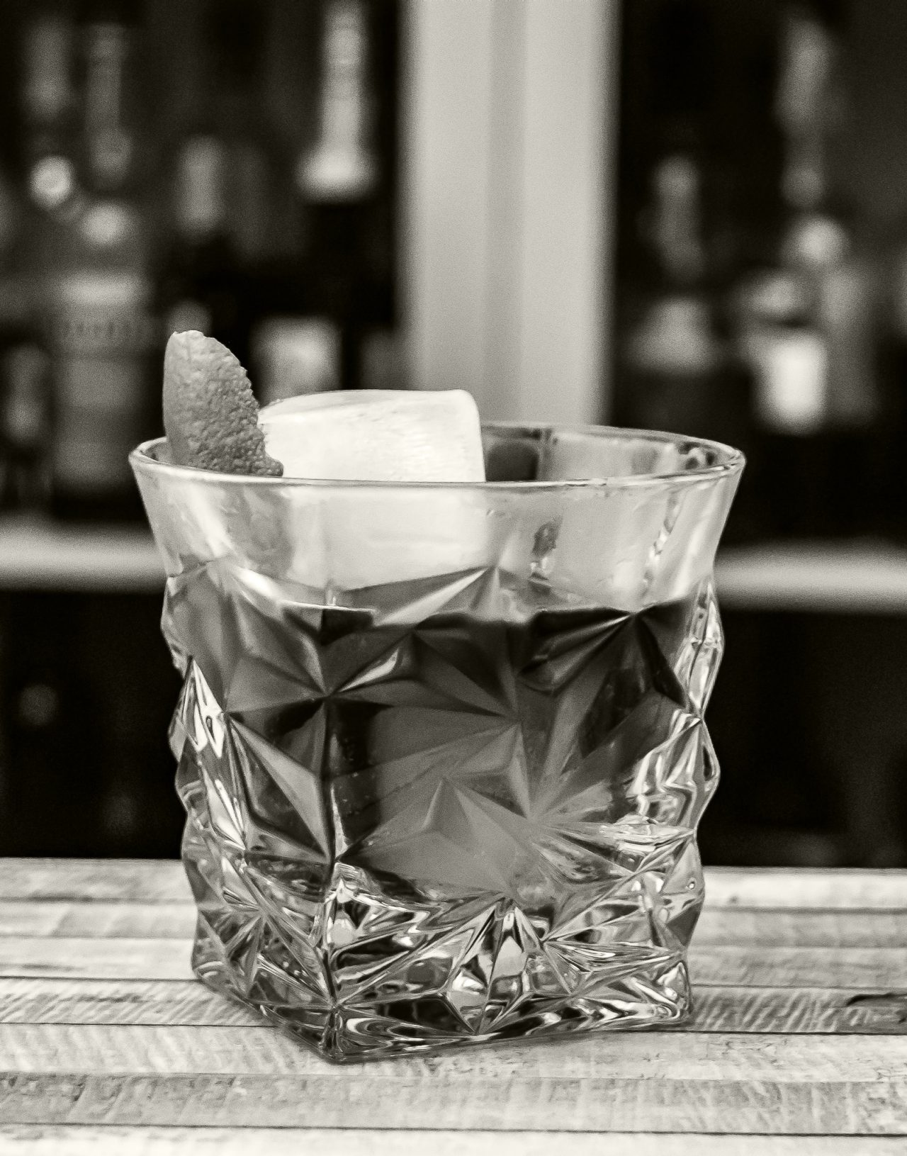 Black and white closeup of an Old Fashioned in a fancy glass