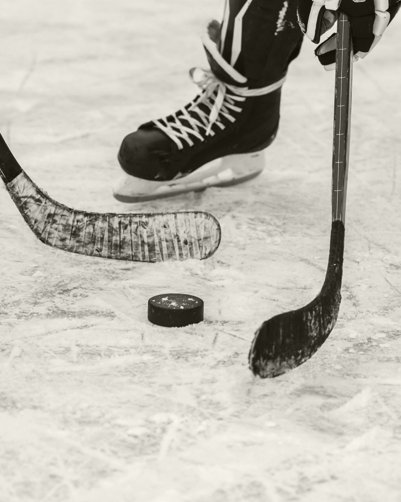 Black and white closeup of two hockey sticks going after hockey puck