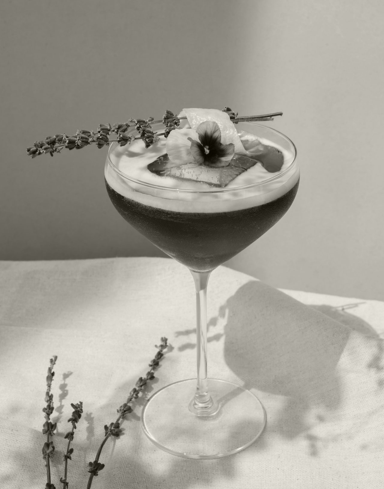 Black and white closeup of a cocktail in a coup glass with flower garnish