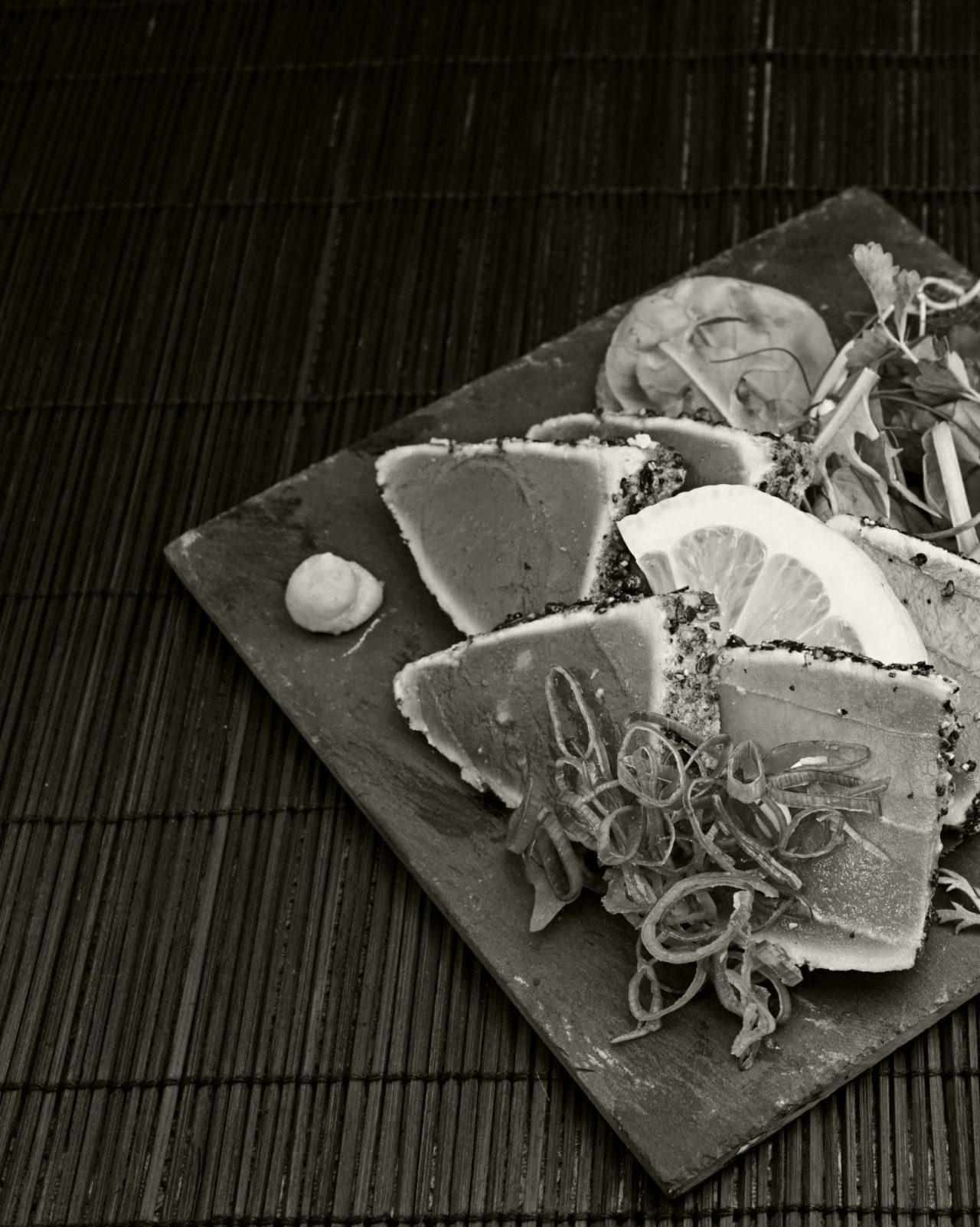 Black and white shot of seared crusted ahi tuna on platter on table
